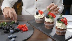 Begrepp av små och medelstora företag och konfekt Kvinnlig bagare som dekorerar den smakliga muffin arkivfilmer