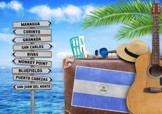 Begrepp av sommarresanden med den gamla resväskan och Nicaragua staden royaltyfri bild