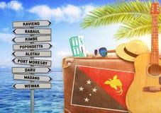 Begrepp av sommarresanden med den gamla resväskan och Papua Nya Guinea Arkivbilder