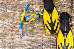 Begrepp av sommarsemestrar Maskering fena, snorkel på rotangbakgrund Fotografering för Bildbyråer