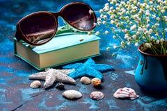 Begrepp av sommarsemestrar Snäckskal, solglasögon och sjöstjärna på ett mörker - blå bakgrund Med kopiera utrymme Lopp- och affär Royaltyfri Fotografi