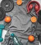 Begrepp av sportar livsstil, hörlurar, hantlar, apelsiner, en flaska av vatten, enskjorta för det utbildande stället för den lekm royaltyfria bilder