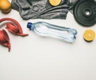 Begrepp av sportar livsstil, hörlurar, hantlar, apelsiner, en flaska av vatten, enskjorta för det utbildande stället för den lekm arkivbild