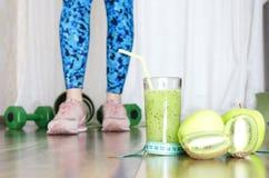 Begrepp av sporten och den sunda livsstilen Kvinnliga ben som står på trägolv nära denmatta sporten och hantlar ny green arkivfoton