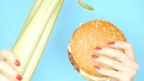 Begrepp av sund och sjuklig mat selleristj?lk mot hamburgare p? en ljus bl? bakgrund kvinnliga h?nder med arkivfoton