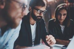 Begrepp av teamworkprocessen på kontoret Ungt lag som tillsammans arbetar på den moderna kontorsvinden för natt suddighet bakgrun fotografering för bildbyråer