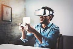 Begrepp av teknologi, dobbel, underhållning och folk Afrikansk man som tycker om virtuell verklighetexponeringsglas, medan koppla arkivbilder