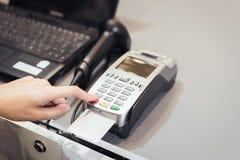 Begrepp av teknologi i köpande, utan att använda kassa Slut upp av handbrukskreditkorten som nallar maskinen för att betala arkivfoton