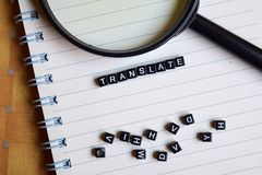 Begrepp av Translate ordet på träkuber med böcker i bakgrund arkivbild