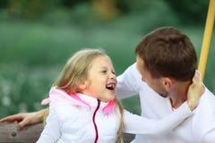 Begrepp av utbildning: farsa och dotter som spelar i parkera på ett S Fotografering för Bildbyråer