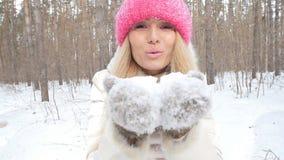 Begrepp av vinterunderhållning Den unga kvinnan i vinter parkerar med insnöade händer stock video