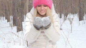Begrepp av vinterunderhållning Den unga kvinnan i vinter parkerar med insnöade händer lager videofilmer