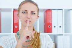 Begrepp för affärshemlighet Ung danande för affärskvinnan hyssjar tecknet Royaltyfri Fotografi
