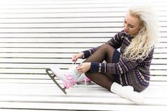 Begrepp för aktivitet för vintersport Flickan sätter på skridskor Arkivbild