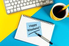 Begrepp för arbetsställe - kontorsskrivbord med anmärkningar om lycklig helg med morgonkaffekoppen arkivfoto