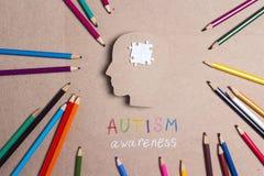 Begrepp för autismmedvetenhetdag med blyertspennor för för pusselhjärnsymbol och färg arkivbilder