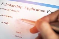Begrepp för avtal för stipendiumansökningsblankettdokument med pennan i handen för lånutbildning arkivfoton