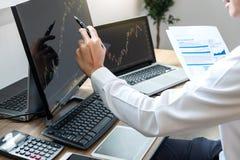 Begrepp för börsmarknad, materielmäklare som ser grafarbete och analyserar med skärmskärmen som pekar på datan royaltyfri bild