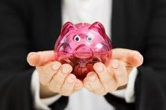 Begrepp för besparingar för affärsvinst - hållande spargris för kvinna i mummel Royaltyfri Foto