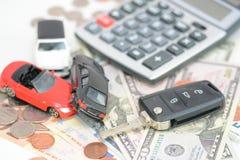 Begrepp för bilförsäkring med leksakbilar, biltangent, mynt och räkningar royaltyfri bild