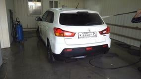 begrepp för bilrenlighetclose som tvättar sig upp Lokalvårdbil genom att använda högtryckvatten lager videofilmer