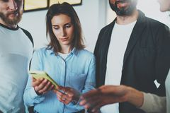 Begrepp för Coworkersaffärsmöte Unga kvinnor som rymmer den mobila smartphonehanden och diskussionsnyheterna med hennes kollegor royaltyfria foton
