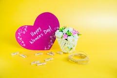 Begrepp för dag för kvinna` s Korg med blommor och pappers- hjärta med lycklig dag för kvinna` s på guld- bakgrund Arkivbilder