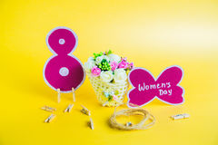 Begrepp för dag för kvinna` s Korg med blommor, pappers- nummer 8 och den pappers- fjärilen med dag för kvinna` s på guld- bakgru Royaltyfria Bilder