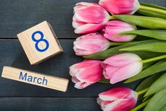 Begrepp för dag för kvinna` s Rosa tulpan och datumet för mars 8th på blå bakgrund Arkivfoton