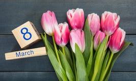Begrepp för dag för kvinna` s Rosa tulpan och datumet för mars 8th på blå bakgrund Arkivbild
