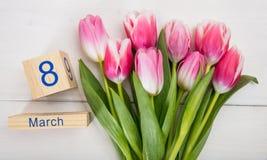 Begrepp för dag för kvinna` s Rosa tulpan och datumet för mars 8th på vit bakgrund Arkivfoto