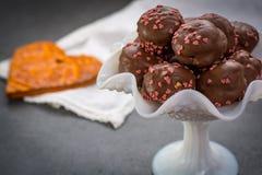 Begrepp för dag för valentin` s, chokladprofiteroles med rosa hjärtor Royaltyfria Bilder