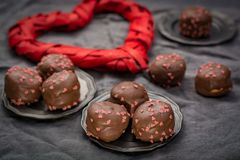 Begrepp för dag för valentin` s, chokladprofiteroles med rosa hjärtor Royaltyfria Foton