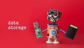 begrepp för datalagring Roboten leker med usb-exponeringspinnen och minneskortet på röd bakgrund Sikt för kopieringsutrymmemakro royaltyfri foto