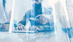 Begrepp för dubbel exponering Coworking process i ett soligt kontor Man arbete på datoren på den wood tabellen Trycka på för kvin Royaltyfri Bild