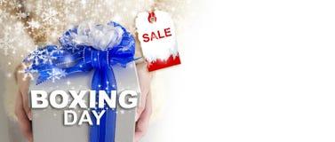 Begrepp för försäljning för boxningdag av händer för ung kvinna som rymmer silvergåvan Arkivfoto