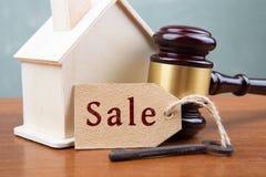 Begrepp för fastighetförsäljningsauktion - auktionsklubban och huset modellerar på trätabellen arkivbilder