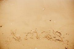 Begrepp för glad jul, lyckliga ferier Xmas-text på den sandiga stranden arkivbild