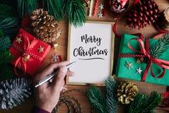 Begrepp för glad jul med den mänskliga handen som skriver kort med gåvaasken arkivbilder