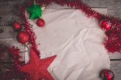 Begrepp för glad jul med röd garnering på träbräde royaltyfria foton