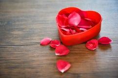 Begrepp för hjärta för valentindagförälskelse/öppen röd hjärtaask som dekoreras med kronblad för röda rosor på trä arkivbilder