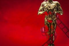 Begrepp för Hollywood filmutmärkelser med den skinande metalliska filmutmärkelsen som slås in i remsa för celluloidfilm på röd ma royaltyfria foton