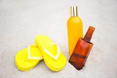 Begrepp för hudomsorg - flipmisslyckanden och solkrämflaskor i sand Arkivbilder