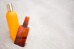 Begrepp för hudomsorg - solkrämflaskor i sand royaltyfria foton