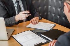 Begrepp för jobbintervju, hög chef som läser en meritförteckning under ett sökande för möte för ung man för anställd för jobbinte arkivfoto