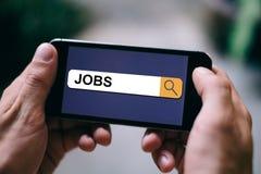 Begrepp för jobbsökande - jobb som är skriftliga i sökandestång på mobil skärm- eller smartphoneskärm royaltyfri fotografi