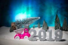 Begrepp för jul eller för nytt år Leksakbil som bär en julgran till och med skogen i snöfall Semestra dekorerad bakgrund royaltyfri fotografi