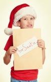Begrepp för jul för vinterferie - pojke i hatt med bokstaven till santa på isolerad vit Arkivbild