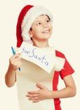 Begrepp för jul för vinterferie - pojke i hatt med bokstaven till santa på isolerad vit Fotografering för Bildbyråer