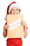 Begrepp för jul för vinterferie - pojke i hatt med bokstaven till santa på isolerad vit Royaltyfri Foto